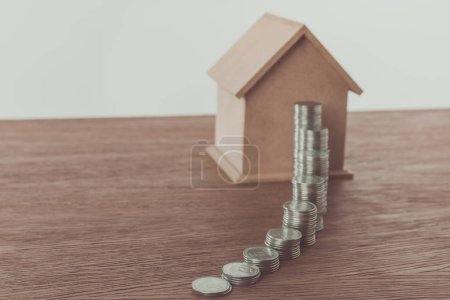 stacks of coins and small wooden house on brown tabletop, saving concept