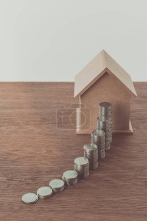 stacks of coins and small wooden house on wooden table, saving concept