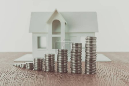stacks of coins on wooden table in front of small wooden house, saving concept