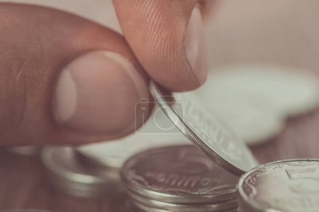 close up of man stacking coins on wooden table, saving concept