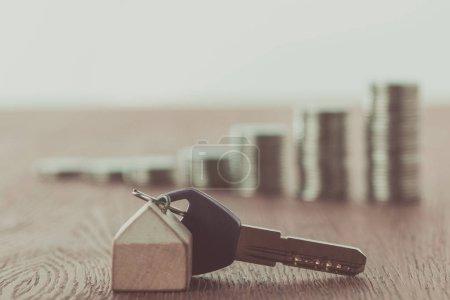 Photo pour Clé avec bijou près de piles de pièces de monnaie sur la table, sauver le concept - image libre de droit