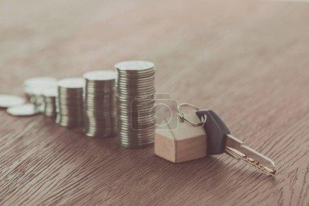 Foto de Llave con Abalorio cerca de pilas de monedas en mesa de madera, concepto de ahorro - Imagen libre de derechos