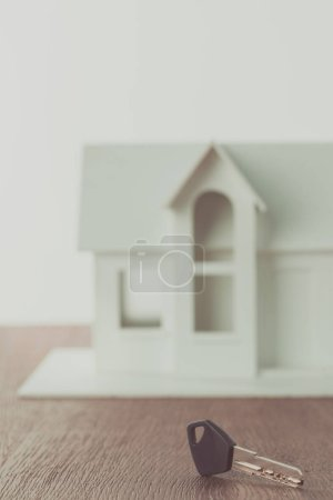 key and white small wooden house on tabletop, saving concept