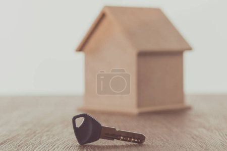 key and small house on wooden table, saving concept