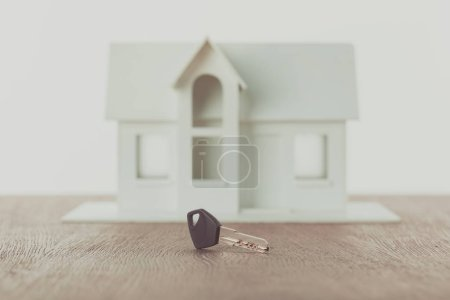 key and small wooden house on tabletop, saving concept