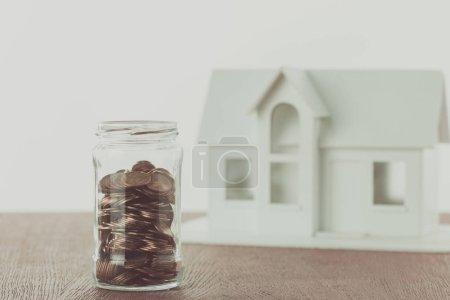 pot de pièces et petite maison en bois sur la table, concept d'économie