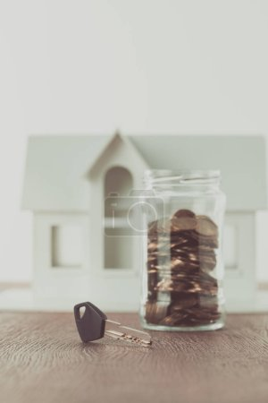 Photo for Key near jar of coins on tabletop with small house on background, saving concept - Royalty Free Image