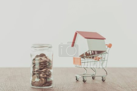 small wooden house on supermarket cart, jar of coins on wooden table, saving concept