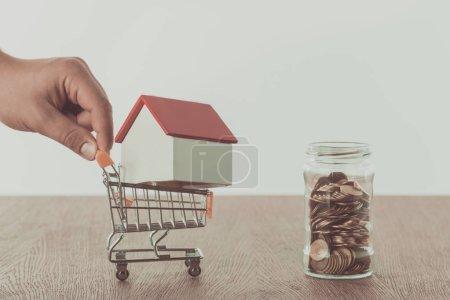 Photo pour Image recadrée de l'homme tenant petit chariot de supermarché avec maison, concept d'économie - image libre de droit