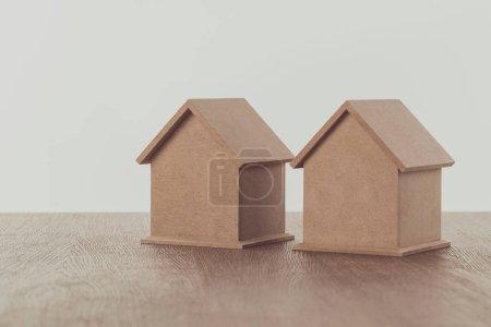 Photo pour Deux petites maisons en bois sur le dessus de table en bois, sauver la notion - image libre de droit