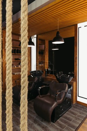 Photo for Close-up view of ropes and empty leather chairs and sinks in modern barbershop - Royalty Free Image