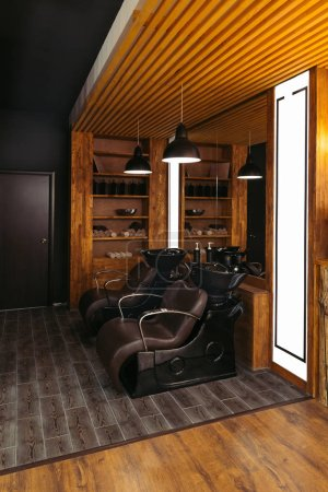 empty leather chairs and sinks in modern barber shop