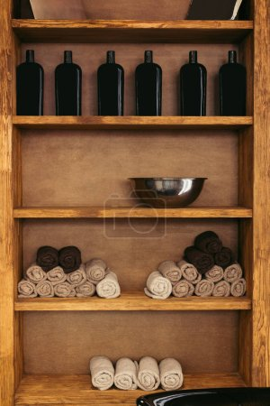 empty metal bowl, rolled towels and glass bottles on wooden shelves in barbershop