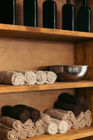 empty metal bowl, rolled towels and glass bottles on wooden shelves