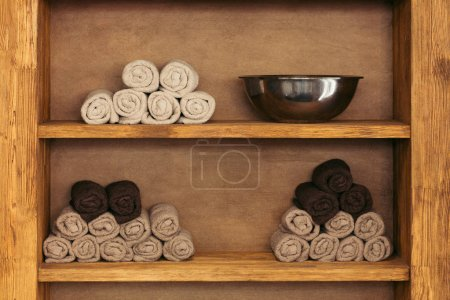 close-up view of empty metal bowl and rolled towels on wooden shelves