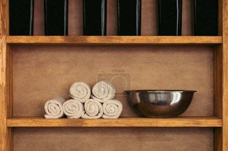 close-up view of empty metal bowl, rolled towels and glass containers on wooden shelves