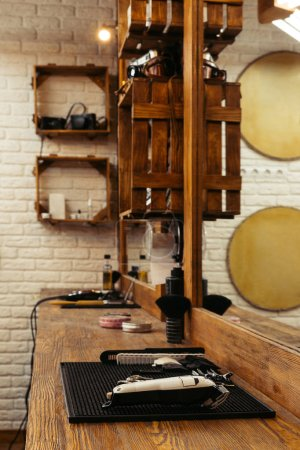 professional barber tools on wooden shelf and mirror at modern barbershop