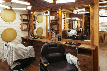 empty chairs reflected in mirrors in modern barbershop