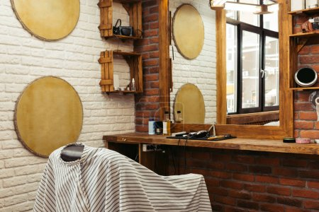 modern barbershop interior and professional barber tools on wooden shelf at mirror