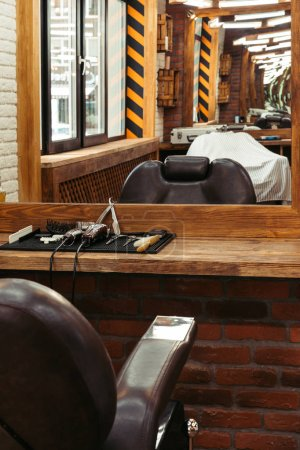 Photo for Modern barbershop interior reflected in mirror and professional barber tools on wooden shelf - Royalty Free Image