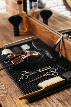 set of various professional barber tools and mirror in barbershop
