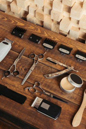 high angle view of various professional barber tools on wooden surface in hair salon