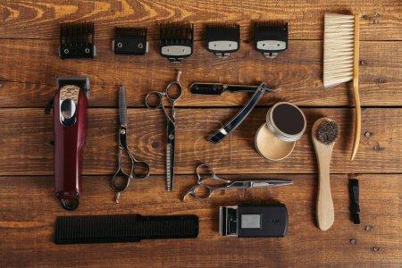 Photo pour Vue de dessus de divers outils de coiffeur professionnel sur une surface en bois dans un salon de coiffure - image libre de droit