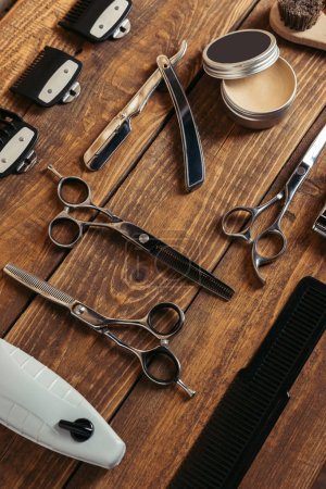 high angle view of various professional barber tools on wooden surface in barbershop