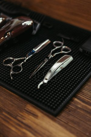 close-up view of professional scissors and straight razor on wooden shelf in barbershop