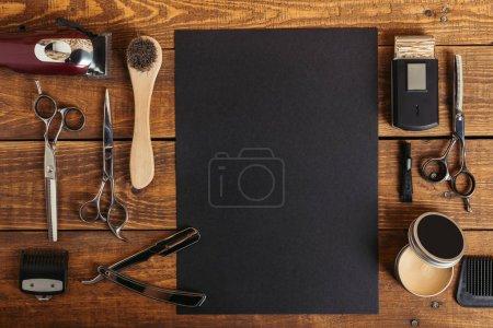 Photo pour Vue du dessus des outils professionnels de coiffeur et carte noire vierge sur table en bois - image libre de droit
