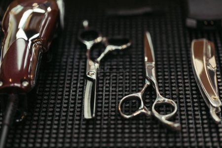 Photo for Close-up view of scissors, electric clipper and straight razor in barbershop - Royalty Free Image