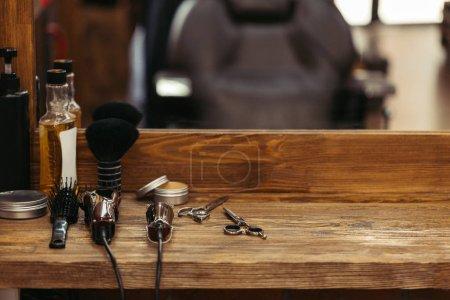 Photo pour Outils de coiffeur sur étagère en bois et miroir dans le salon de coiffure - image libre de droit