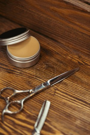 close-up view of scissors and container with hair wax on wooden table