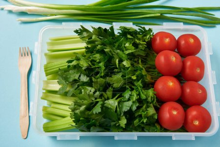 close up view of fork and food container full of fresh tomatoes, parsley and celery on blue background