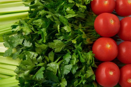 full frame of fresh tomatoes, celery and parsley background