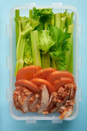 top view of food container full of healthy food on blue backdrop