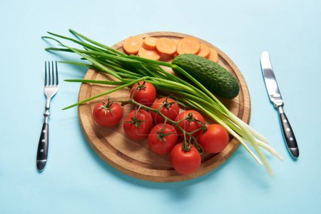close up view of cutlery and assorted fresh vegetables on wooden cutting board on blue backdrop