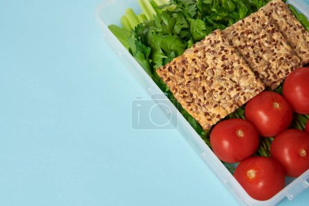 close up view of food container full of healthy vegetables and cookies isolated on blue