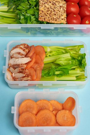 close up view of arrangement of food containers full of fresh healthy food on blue background