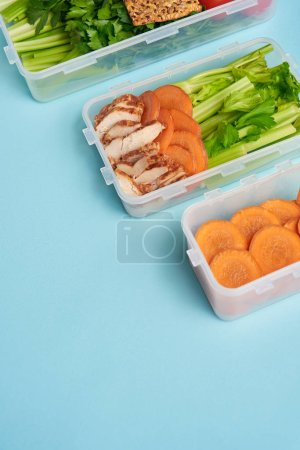 close up view of arrangement of food containers with fresh healthy vegetables and meat isolated on blue
