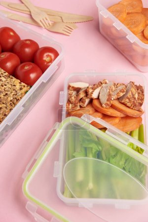 close up view of healthy food arranged in food containers on pink backdrop