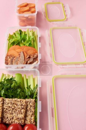 close up view of healthy fresh food arranged in food containers on pink backdrop