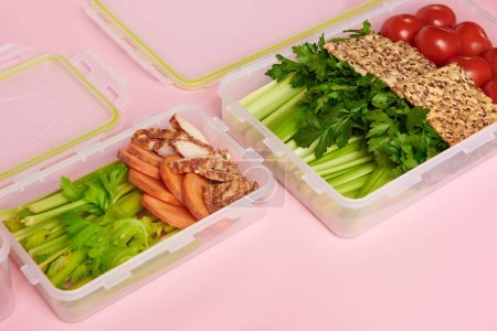 close up view of healthy vegetables and cookies arranged in food containers on pink backdrop