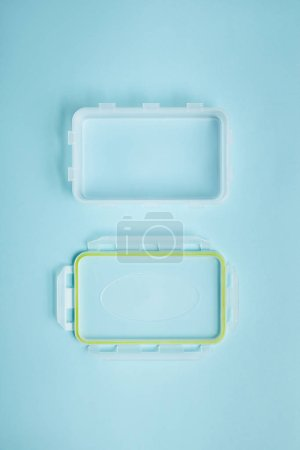 top view of empty food container with cover isolated on blue