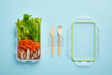top view of cutlery and food container full of healthy meal isolated on blue