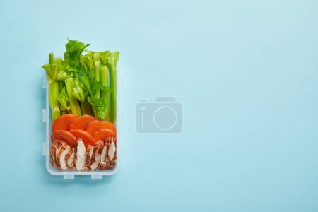 top view of food container full of healthy meal isolated on blue