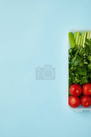 top view of food container full of healthy vegetables isolated on blue