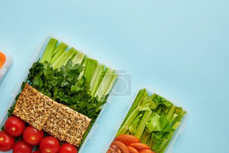 top view of arrangement of food containers with fresh healthy vegetables and cookies with seeds isolated on blue