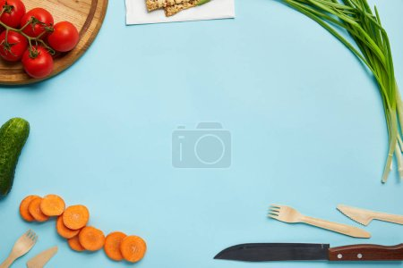 Photo for Top view of assorted fresh vegetables, cookies and cutlery isolated on blue - Royalty Free Image