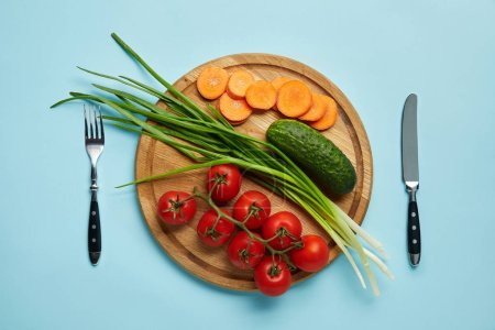 Photo for Top view of cutlery and assorted fresh vegetables on wooden cutting board isolated on blue - Royalty Free Image